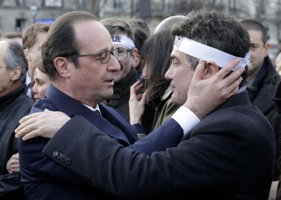 El presidente francés Hollande saluda a uno de los sobrevivientes de Charlie Hebdo. Foto: Reuters