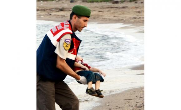 Soldado lleva a Aylan Kurdi, el niño sirio hallado ahogado en una playa de Turquía.