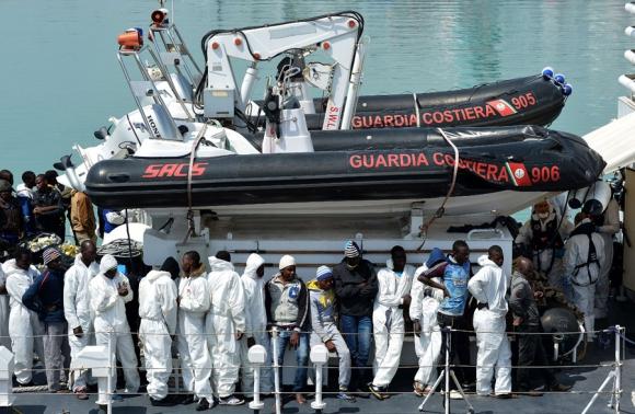 Un grupo de migrantes africanos espera para desembarcar en Catania. Foto: AFP
