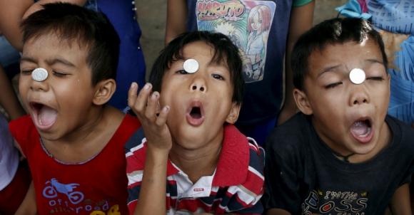 Niños filipinos juegan con monedas durante la tradicional celebración de Nuestro Señor Jesucristo en Quezón, Filipinas. Foto: Reuters.