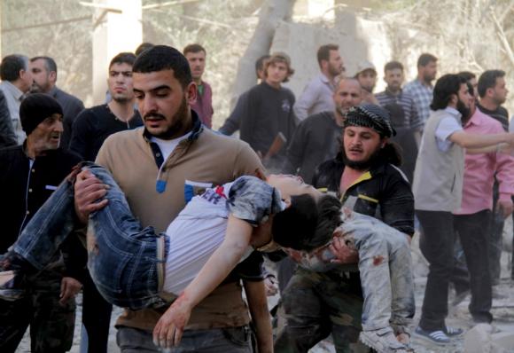 Hombres cargan a niños heridos por ataque de un coche bomba de las fuerzas leales a  Bashar al-Assad. Foto: Reuters.