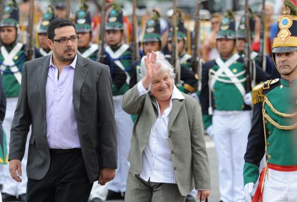 Lucia Topolansky y el diputado Alejandro Sánchez pasando revista al batallón Florida. Foto: AFP