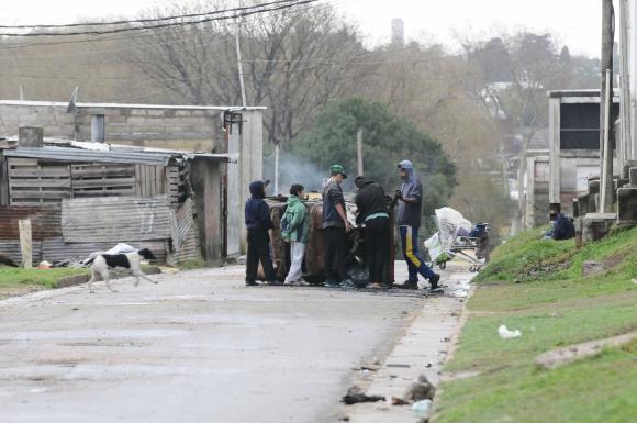 En el asentamiento, jóvenes desguazan auto. Cerca, un carrito de supermercado. Foto: D.Borrelli.