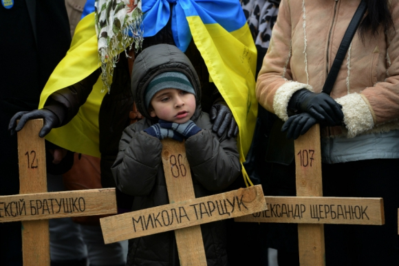 Un niño se apoya en una cruz de madera que honra a las personas asesinadas en la revuelta de la plaza Maidan en Ucrania un año atrás. Foto: AFP.