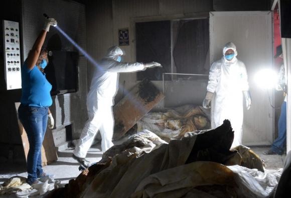 Miembros del equipo médico forense en el crematorio privado. Foto: AFP