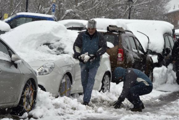 Franceses caminan al costado de autos tapados por la nieve. Foto: AFP
