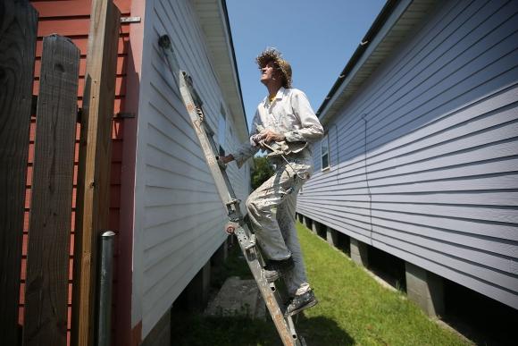 Un hombre pinta su casa reconstruida tras el huracán. Foto: AFP.