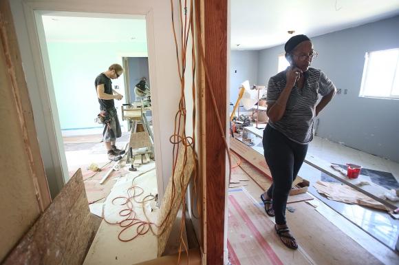 Una mujer recorre su casa mientras voluntarios la ayudan a reconstruirla en Nueva Orleans. Foto: AFP.