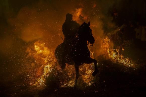 Un hombre cabalga su caballo a través de las llamas durante la celebración anual de las