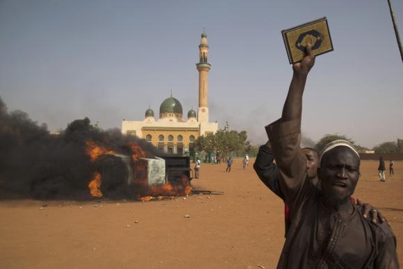 Un hombre sostiene el Corán durante las protestas en Níger en contra de la representación del profeta en el semanario satírico Charlie Hebdo. Foto: Reuters.