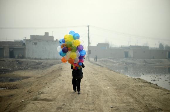 Arsh, un vendedor de globos de 19 años, busca clientes mientras recorre las calles de Kabul. Foto: AFP.