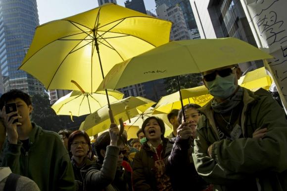 Manifestantes sostienen paraguas amarillos en señal de protesta contra la detención de los líderes del grupo prodemocrático