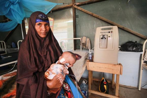 Una anciana sostiene a su nieto recién nacido, mientras que su hija, que  padece una enfermedad mental, se recupera luego del parto. Foto: Tom Maruko /MSF