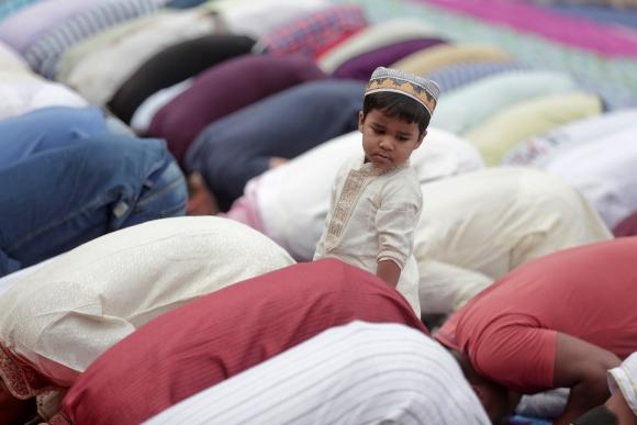 Un niño se pone de pie mientras la gente reza para celebrar la