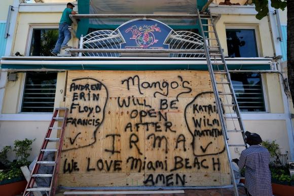 En las costas de Florida ponen tableros y maderas en las puertas de sus casas y comercios ante la llegada del huracán Irma. Foto: AFP