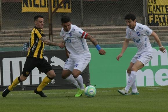 Fabián Estoyanoff intenta centrar ante la marca de Diego Polenta y Jorge Fucile. Foto: Francisco Flores
