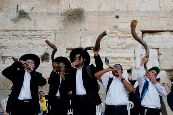 Varios judíos ultraortodoxos tocan el shofar mientras unos fieles rezan al Muro de las Lamentaciones. Foto: EFE