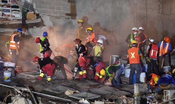 Entre nubes de polvo, expertos de las unidades de rescate y bomberos buscan sobrevivientes en un edificio destruido. Foto: AFP