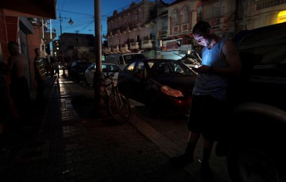 Un habitante de San Juan logra comunicarse a través de su teléfono. Foto: Reuters