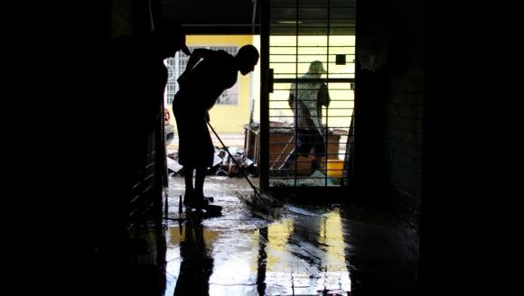 Un habitante de Comercio, en Puerto Rico, retira el barro que cubre su casa. Foto: AFP