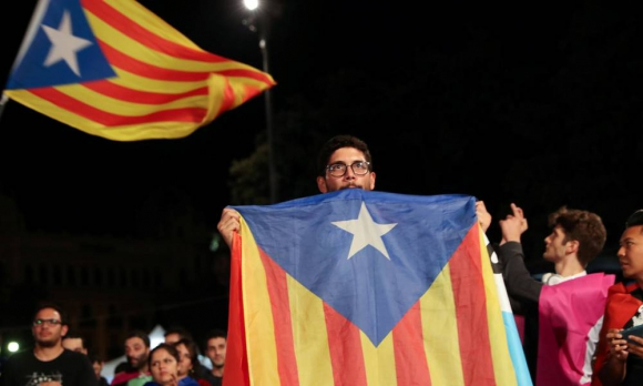 Un hombre posa con una bandera catalana tras el referéndum. Foto: AFP