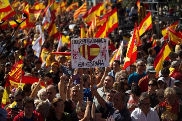 """Un hombre sostiene un cartel con la frase """"Queremos a Cataluña en España"""" durante las protestas. Foto: AFP"""