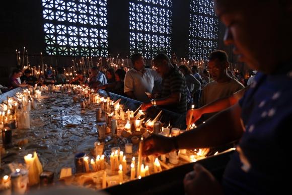 Fieles encienden velas en el santuario tras la peregrinación. Foto: EFE