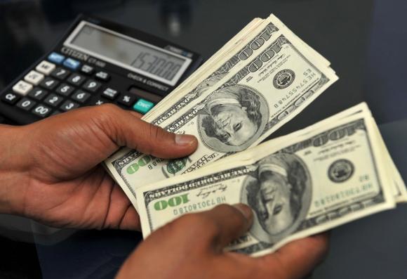 Facturar en dólares al mercado interno es una de las estrategias que usan las empresas uruguayas. Foto: AFP