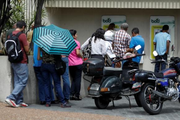 Venezolanos hacen filas en cajeros automáticos para retirar dinero. Foto: Reuters