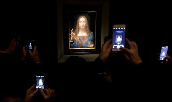 Varias personas fotografían la obra 'Salvator Mundi' del artista Leonardo da Vinci. Foto: EFE