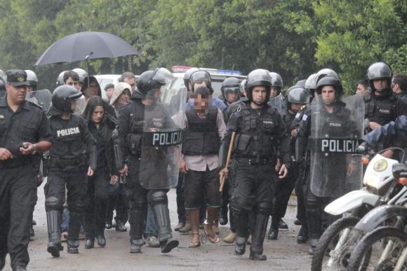 El confeso homicida custodiado por policías durante la reconstrucción. Foto: Marcelo Pinto