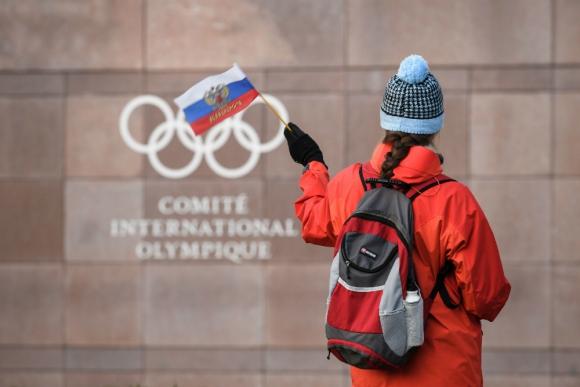 Una aficionada flameando la bandera de Rusia frente al logo del Comité Olímpico Internacional. Foto: AFP