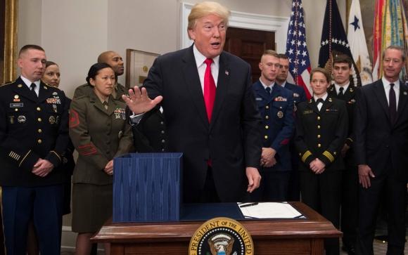 Donald Trump firmando la ampliación para el presupuesto de Defensa. Foto: AFP