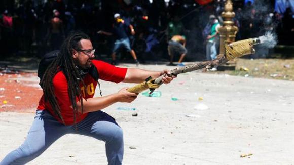 """Sebastián Romero dispara una lanzadera """"casera"""" contra los policías. Foto: Reuters"""
