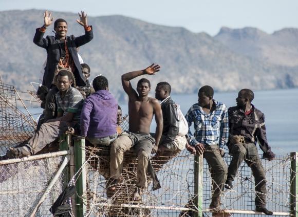 Inmigrantes ilegales de África en la reja divisoria entre Marruecos y Melilla. Foto: AFP