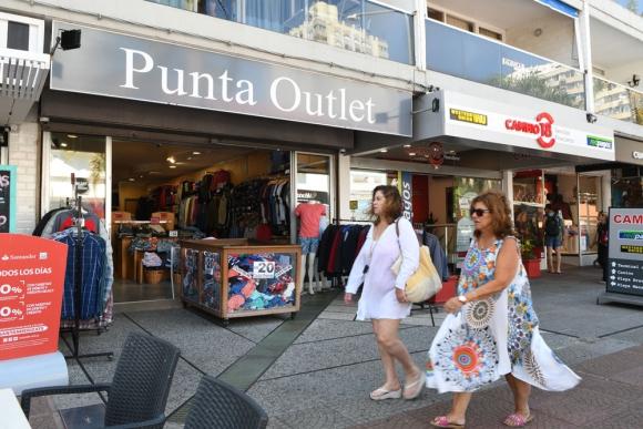 Dos mujeres caminan por Gorlero frente a un local con canastos de ofertas. Foto: D. Borrelli