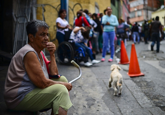 Una mujer espera su turno para comprar alimentos en Caracas. Foto: AFP