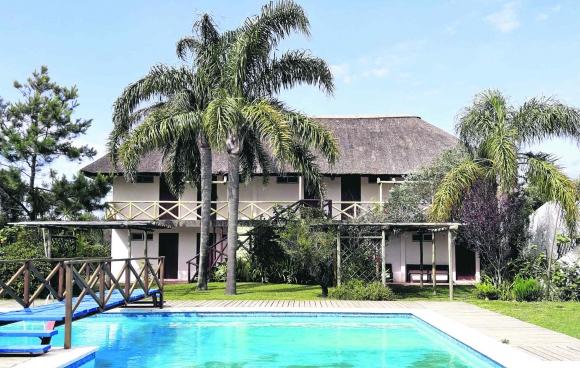 """Relax. """"Nuestros bungalows y el hotel están en el corazón de un parque con una generosa piscina""""."""