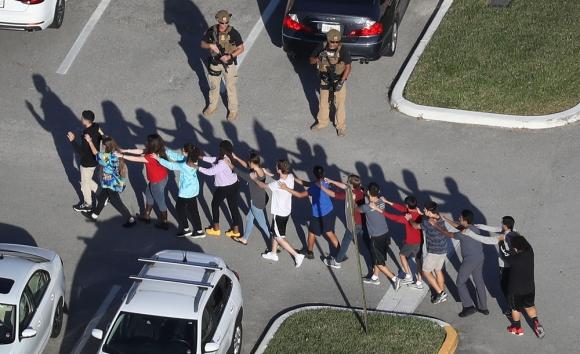 Alumnos del colegio de Parkland salen en fila custodiados por oficiales armados. Foto: AFP