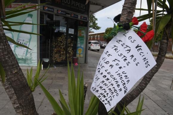 Vecinos y transeúntes improvisaron homenajes a la chica asesinada depositando flores en la puerta. Foto: F. Flores