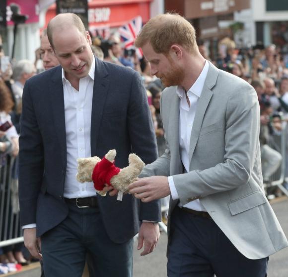 El príncipe Harry y el duque de Cambridge miran a un oso de peluche. Foto: Reuters