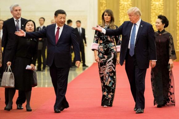 Trump y su esposa junto a autoridades chinas para limar asperezas. Foto: AFP