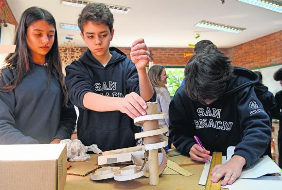 Estudiantes preparan pista de cartón para bolitas. Foto: A. Colmegna