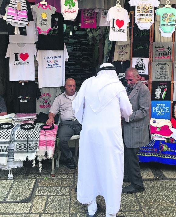 """Un ciudadano árabe conversa con un comerciante que vende camisetas de """"Palestina libre"""" e imágenes de Yasser Arafat. Foto: El País"""