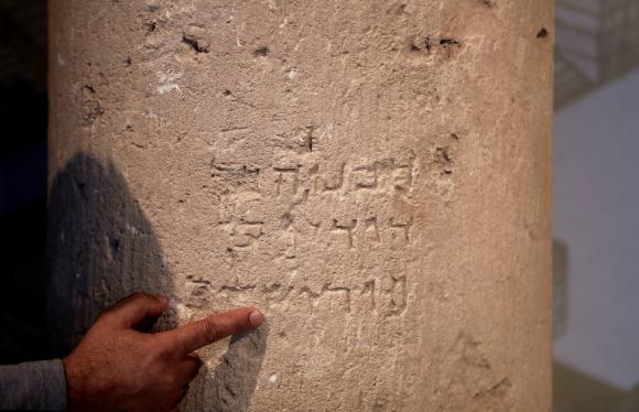 """Un arqueólogo de la Autoridad de Arqueología de Israel (AAI) muestra la piedra que lleva una inscripción de 2.000 años de antigüedad en la que se lee en hebreo """"Jerusalén"""". EFE"""