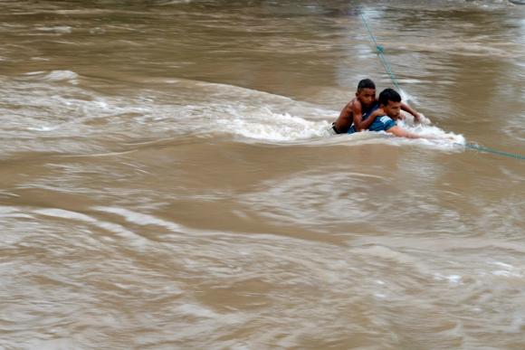 Padre e hijo hondureños curzando el río Goascorán, en la frontera con El Salvador. Foto: Reuters