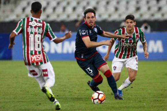 Matías Zunino entre dos jugadores de Fluminense
