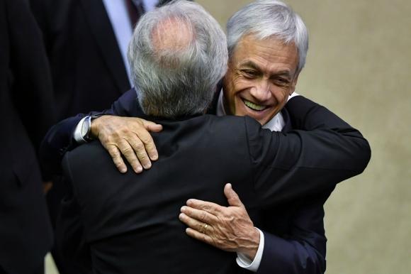 Vázquez saluda a Piñera durante la asunción de Bolsonaro. Foto: AFP.
