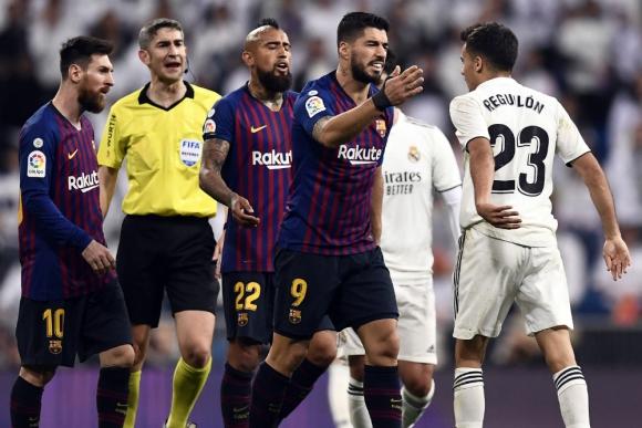 Luis Suárez y en choque con Sergio Reguilón. Foto: AFP