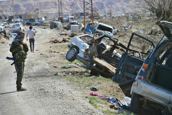 Una combatiente de las Fuerzas Democráticas Sirias mira vehículos dañados cerca de Baghuz. Foto: AFP
